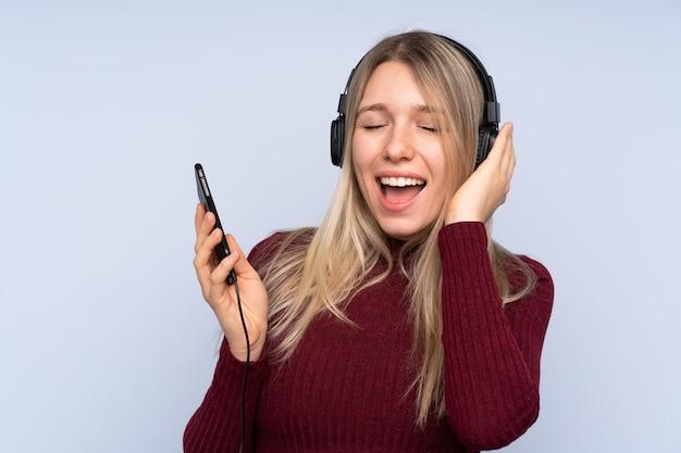 Giovane donna bionda sopra musica d'ascolto isolata della parete blu con un cellulare e un canto