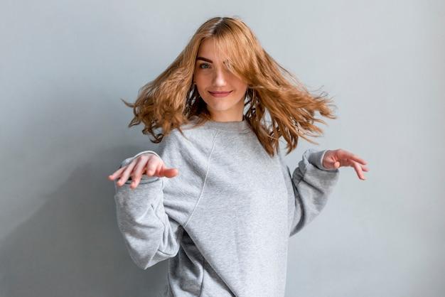 Giovane donna bionda sorridente che balla contro la parete grigia