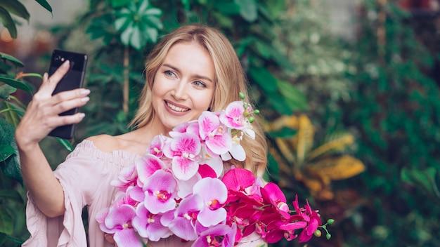 Giovane donna bionda sorridente che giudica orchidea fresca a disposizione che prende autoritratto dal telefono cellulare
