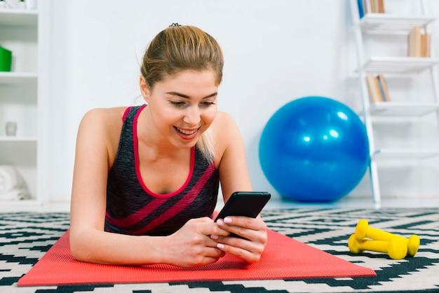 Giovane donna bionda sorridente che si trova sulla stuoia di esercizio rossa facendo uso del telefono cellulare