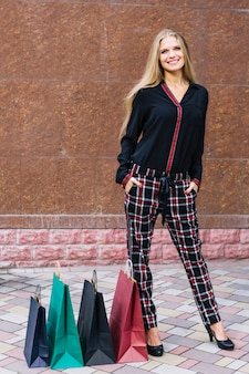 Giovane donna bionda sorridente con le sue mani in tasche che stanno vicino ai sacchetti della spesa variopinti
