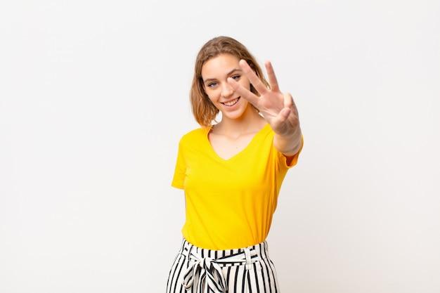 Giovane donna bionda sorridente e guardando amichevole, mostrando il numero tre o terzo con la mano in avanti, conto alla rovescia contro la parete di colore piatto