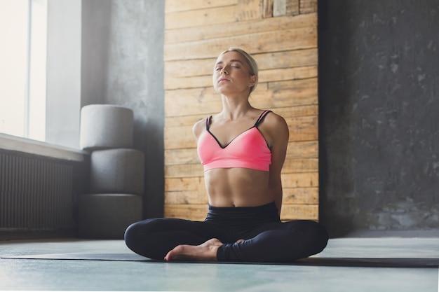 Giovane donna bionda sottile nella classe di yoga facendo esercizi di asana. la ragazza fa la posa del mezzo loto e allunga la schiena. stile di vita sano nel fitness club.