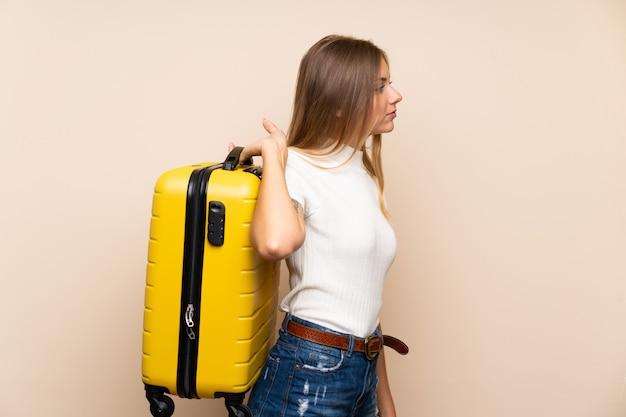 Giovane donna bionda sul muro isolato in possesso di una valigetta vintage