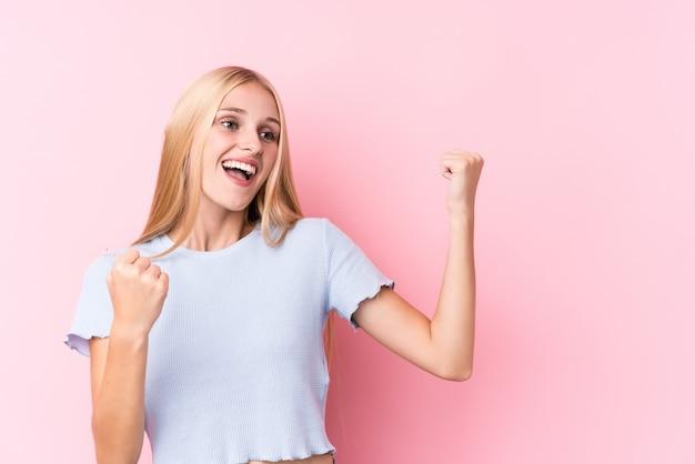 Giovane donna bionda sulla parete rosa che alza pugno dopo una vittoria, concetto del vincitore.