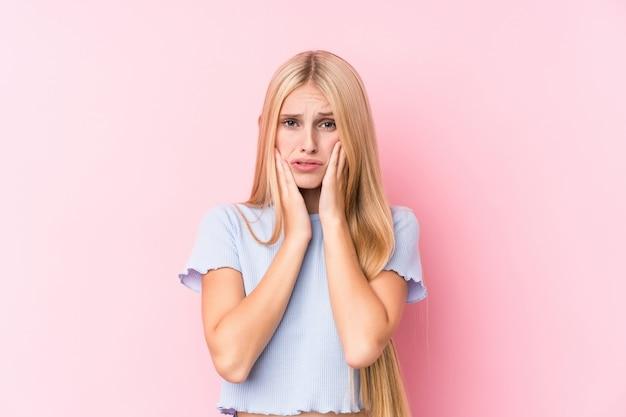 Giovane donna bionda sulla parete rosa che geme e piange sconsolata.