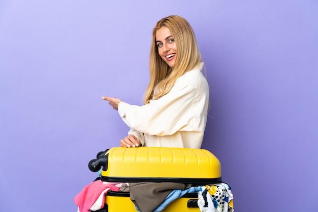 Giovane donna bionda uruguaiana con una valigia piena di vestiti sul muro viola che estende le mani a lato per invitare a venire