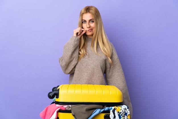 Giovane donna bionda uruguaiana con una valigia piena di vestiti sul muro viola che mostra un segno di silenzio gesto