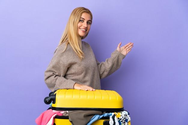 Giovane donna bionda uruguaiana con una valigia piena di vestiti sul muro viola isolato che estende le mani a lato per invitare a venire