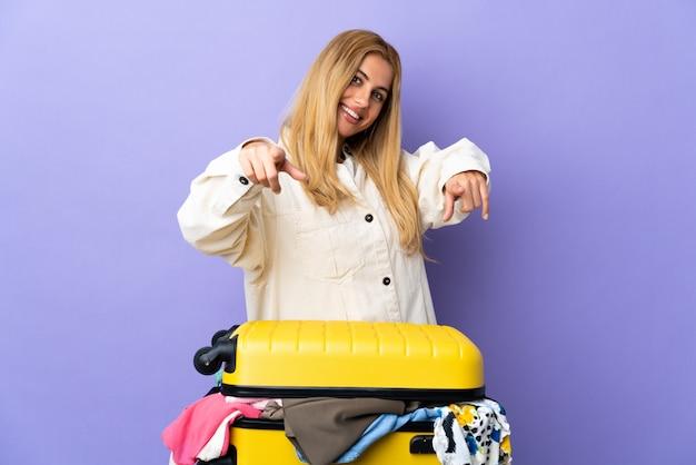 Giovane donna bionda uruguaiana con una valigia piena di vestiti sul muro viola isolato che punta davanti con espressione felice