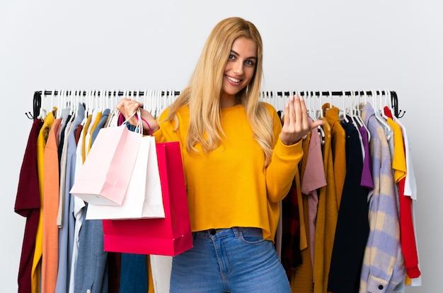 Giovane donna bionda uruguaiana in un negozio di abbigliamento e che tiene i sacchetti della spesa che invita a venire con la mano.