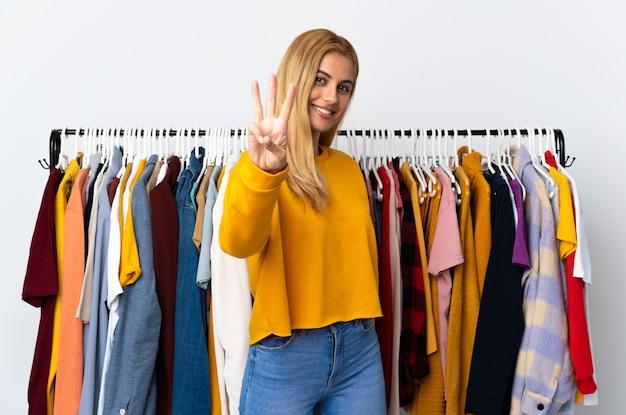 Giovane donna bionda uruguaiana in un negozio di abbigliamento felice e contando tre con le dita
