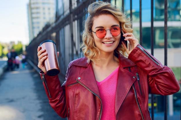 Giovane donna bionda vaga che cammina nella città e che per mezzo dello smart phone. dettagli da vicino. ragazza moderna alla moda con caffè. peli ventosi.
