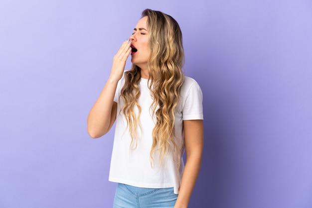 Giovane donna brasiliana isolata sulla bocca spalancata e coning viola con la mano
