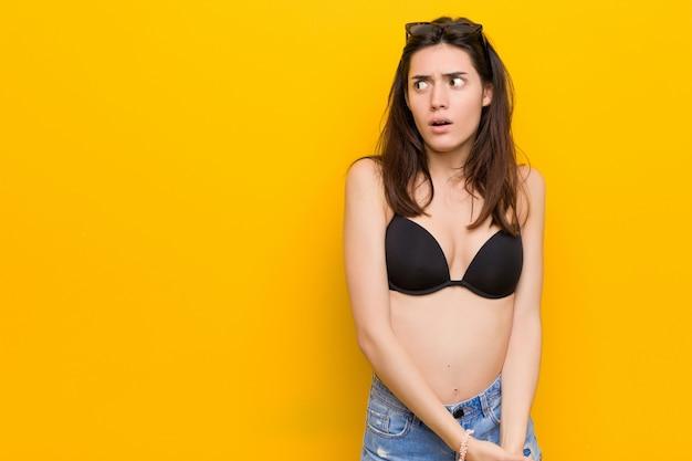 Giovane donna bruna che indossa un bikini scioccato a causa di qualcosa che ha visto.