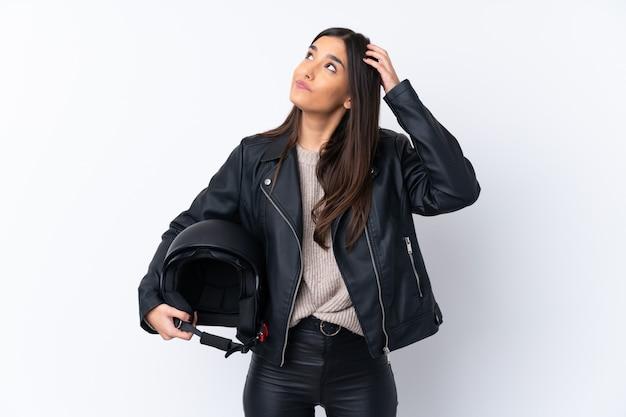Giovane donna bruna con un casco da motociclista che ha dubbi e con espressione del viso confuso