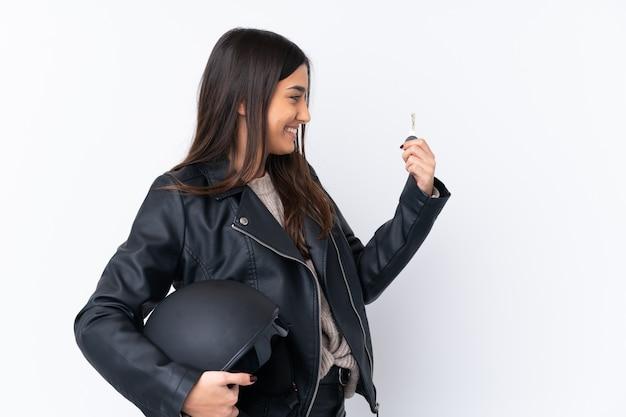 Giovane donna bruna con un casco da motociclista e in possesso di una chiave