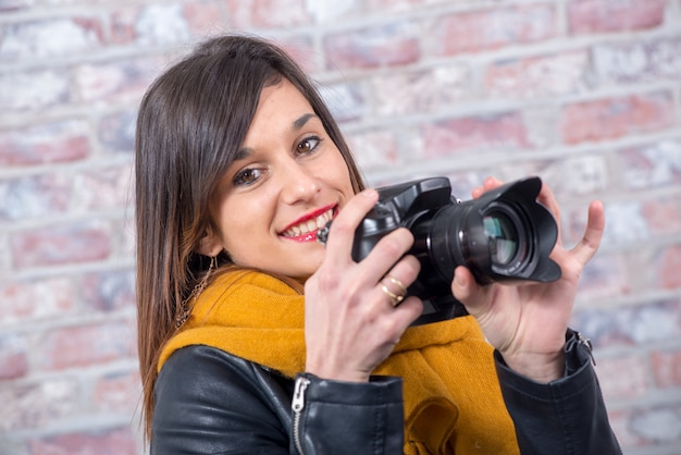 Giovane donna bruna con una macchina fotografica