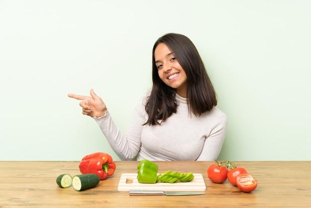 Giovane donna bruna con verdure che punta il dito verso il lato