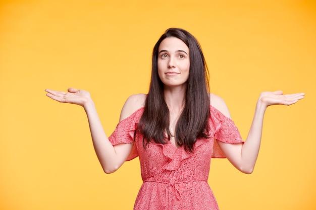 Giovane donna bruna confusa con i capelli lunghi che scrolla le spalle mentre esprime l'incertezza nell'isolamento