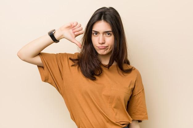Giovane donna bruna contro un muro beige che mostra un gesto di antipatia, pollice verso il basso. concetto di disaccordo.