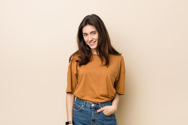 Giovane donna bruna controbeige felice, sorridente e allegra.