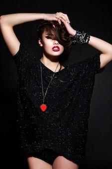Giovane donna bruna in abiti neri