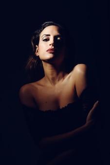 Giovane donna bruna in lingerie nera in illuminazione chiaroscuro.