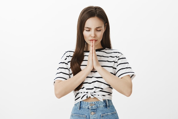 Giovane donna bruna piena di speranza che chiede a dio, supplica o esprime desiderio, prega