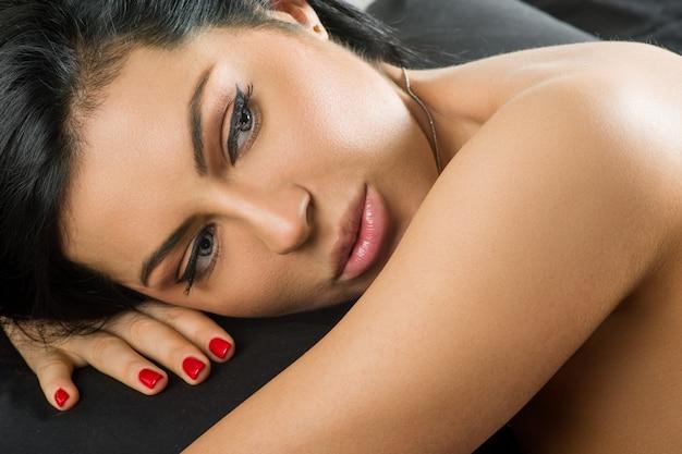 Giovane donna bruna sul letto