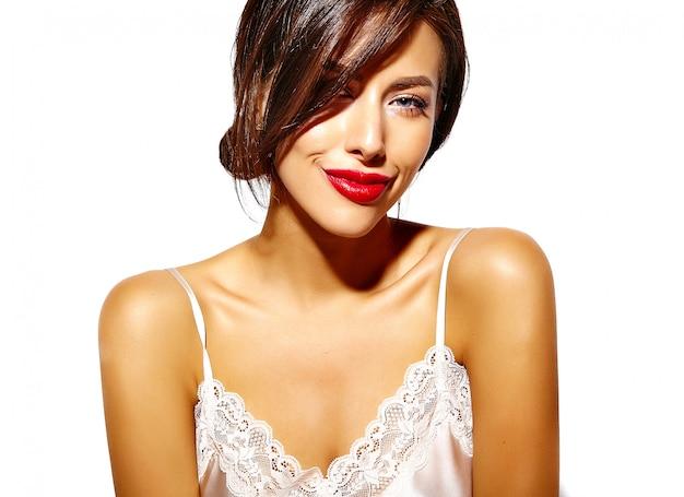 Giovane donna calda elegante sensuale di fascino con le labbra rosse con la vista ubriaca su fondo bianco