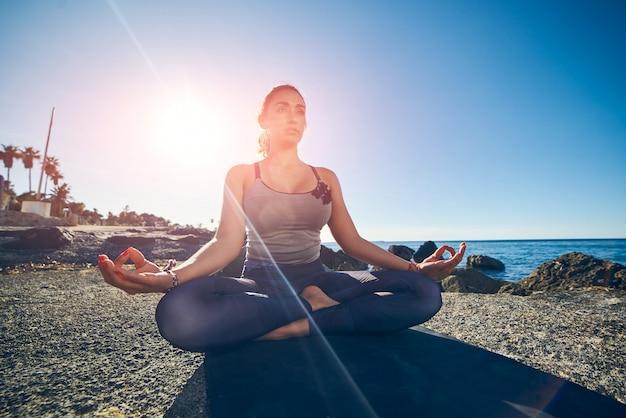 Giovane donna calma che medita su spiaggia contro un bello mare blu.