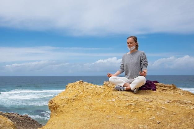 Giovane donna calma nella maschera di protezione che medita all'oceano