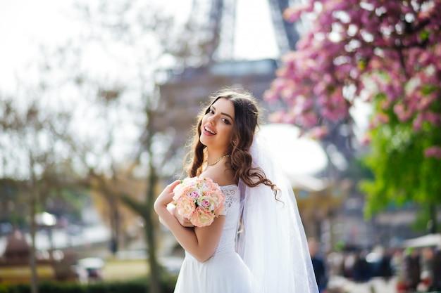 Giovane donna cammina in abito di pizzo bianco, scarpe col tacco alto, parigi,