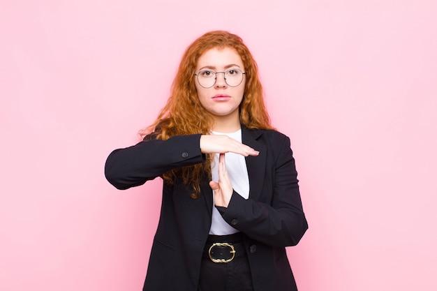Giovane donna capa rossa che sembra seria, severa, arrabbiata e dispiaciuta, facendo segno di timeout contro la parete rosa
