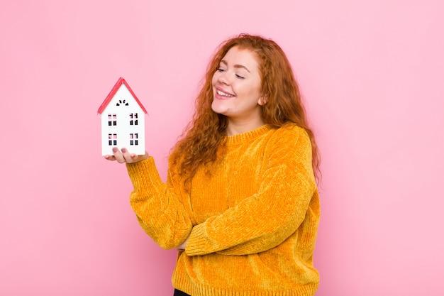 Giovane donna capa rossa che sorride con un'espressione felice e sicura con la mano sul mento, chiedendosi e guardando al lato con un modello della casa