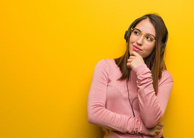 Giovane donna carina ascoltando musica dubitando e confuso