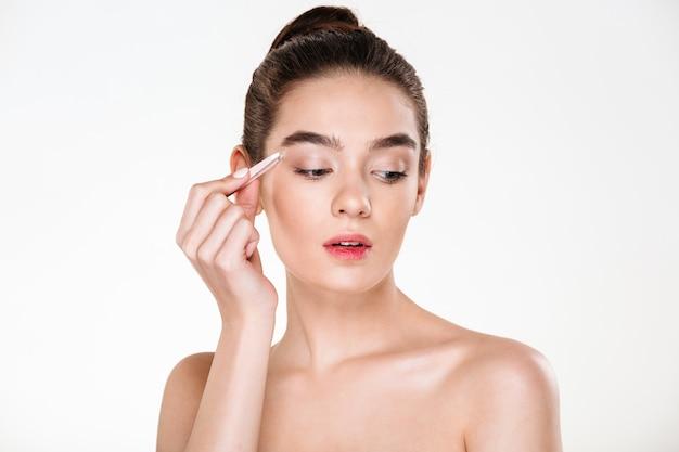 Giovane donna carina con la pelle morbida pizzicando le sopracciglia con una pinzetta