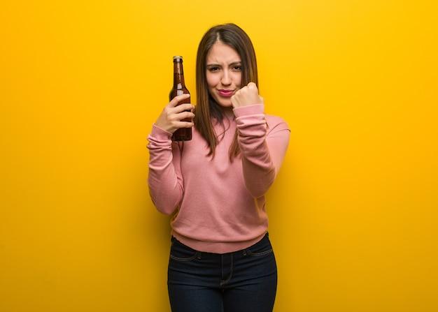Giovane donna carina con una birra che mostra il pugno di fronte, espressione arrabbiata