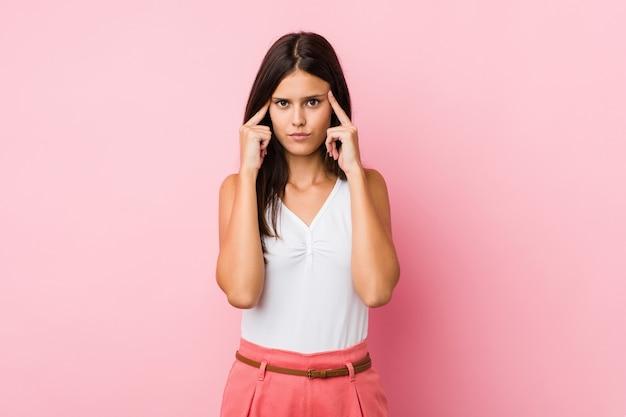 Giovane donna carina focalizzata sul compito, mantenendo l'indice che punta la testa.