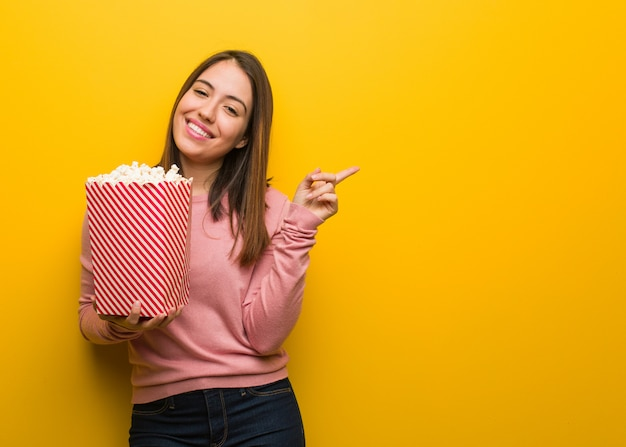 Giovane donna carina in possesso di un secchio di popcorn che punta verso il lato con un dito