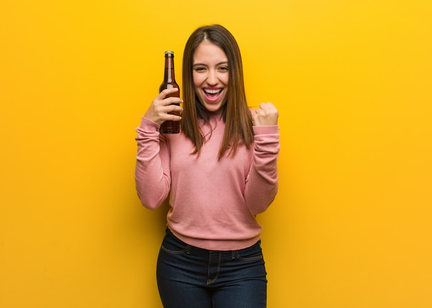 Giovane donna carina in possesso di una birra sorpresa e scioccata