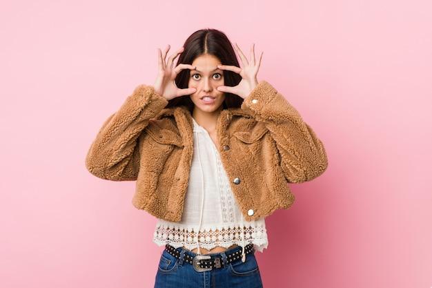 Giovane donna carina tenendo gli occhi aperti per trovare un'opportunità di successo.
