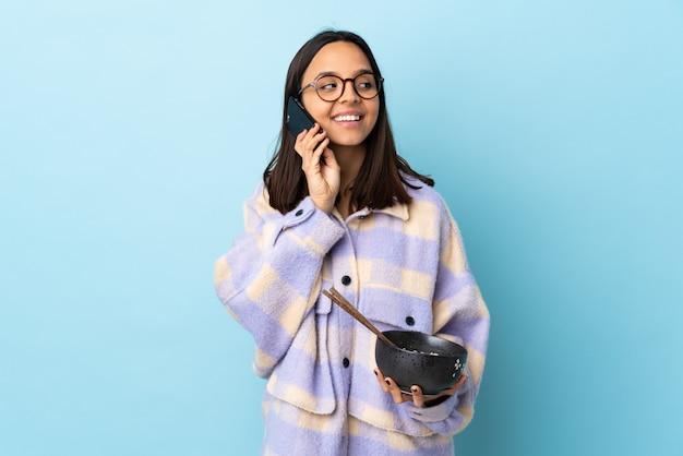 Giovane donna castana che giudica una ciotola piena di tagliatelle sopra il blu isolato che mantiene una conversazione con il telefono cellulare