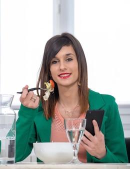 Giovane donna castana che mangia insalata e telefono