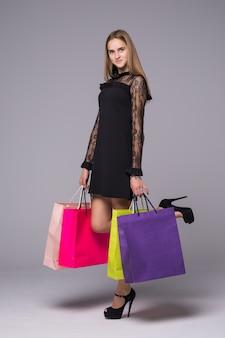 Giovane donna castana che posa con i sacchetti della spesa e che esamina macchina fotografica