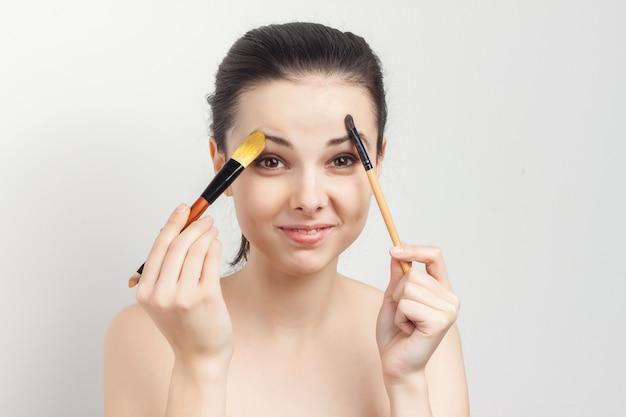 Giovane donna castana che prende cura della sua pelle