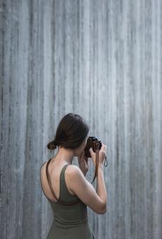 Giovane donna castana che prende un tiro con la macchina fotografica