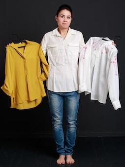 Giovane donna castana che sceglie una camicia di due