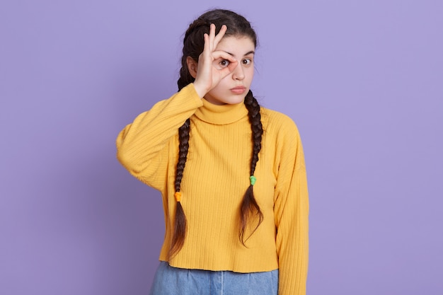 Giovane donna castana che spinge segno giusto e che la copre occhio, posando isolato sopra la parete lilla